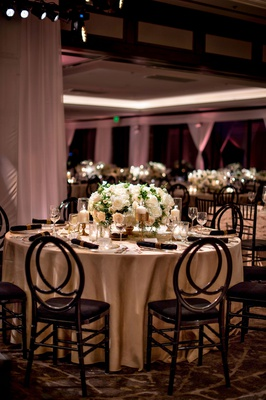 wedding reception round table black chairs beige linen low centerpiece white flowers gold candle