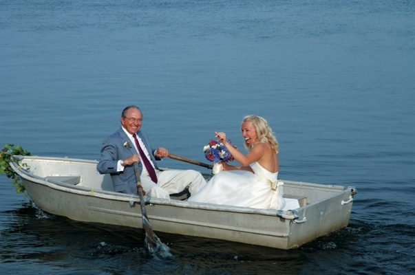 Father of bride rows oars of rowboat with bride in boat