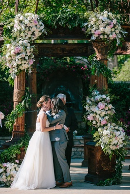 bride in winnie couture, bride in art lewin suit kiss after the vow exchange