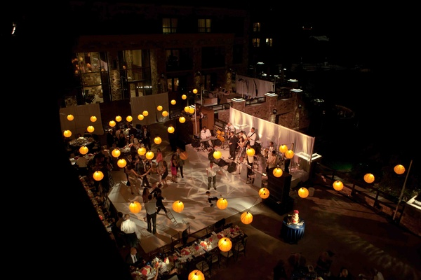 Paper lanterns strung above wedding dance floor