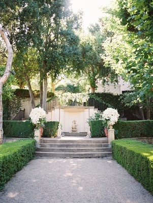 green courtyard white floral arrangements shrubbery altar in outdoor ceremony space estate