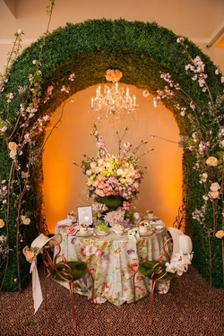 Floral-print tablescape under hedge archway with chandelier