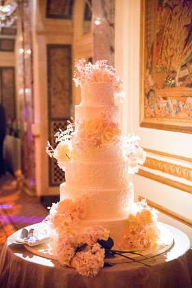 Sylvia Weinstock six-tier white wedding cake with intricate detailing and fresh flowers