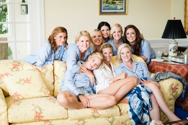 Bride on yellow couch with bridesmaids in light blue pajamas men's button down shirts