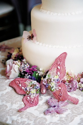 White wedding cake with pink and purple butterflies and colorful flowers