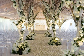 Tented wedding ceremony with trees wrapped with white roses and hydrangeas