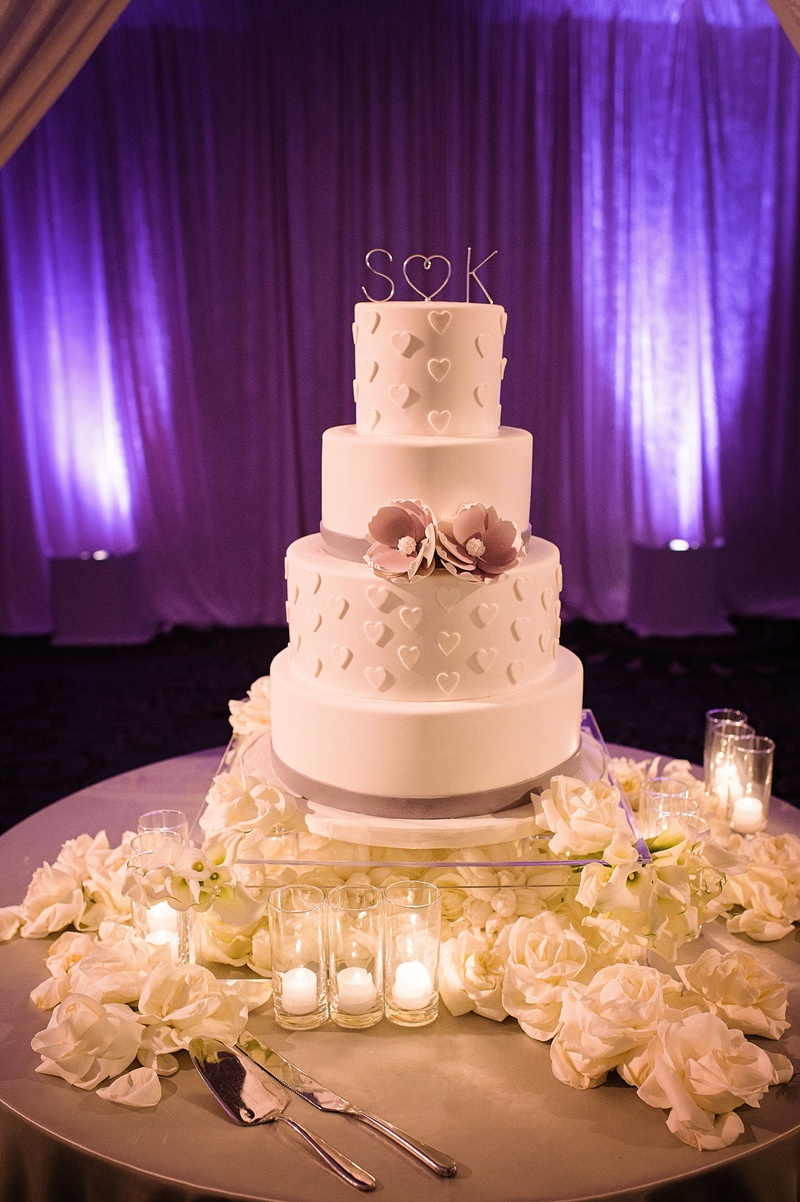 Four layer white wedding cake with heart design and purple sugar flower ribbon white flowers lucite