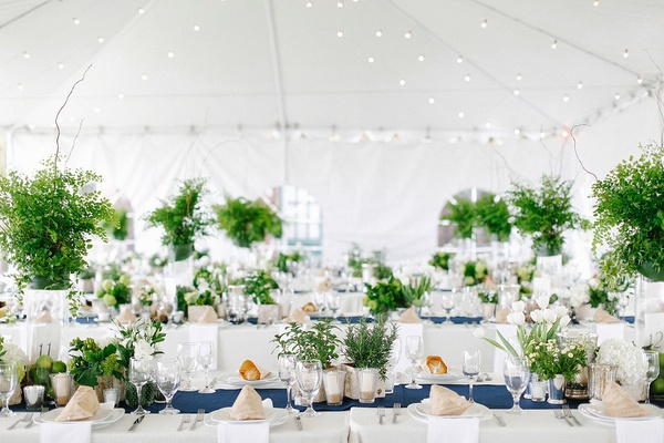 Tent wedding reception with nautical theme, navy blue table runner and greenery centerpieces