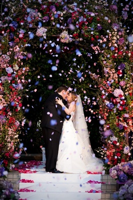 Bride and groom kissing under floral canopy