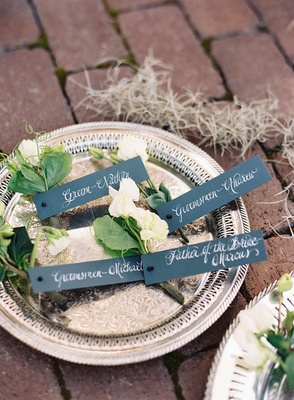 Silver tray platter with boutonniere white flower green leaves tags with calligraphy naming recipien