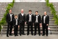 groom groomsmen charcoal gray pink tie in front of steps greenery on handrail