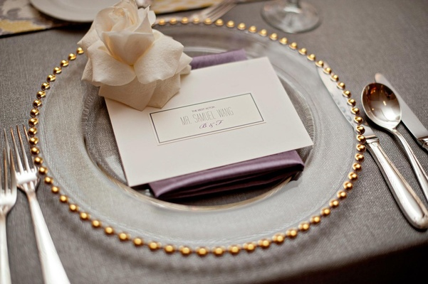 Gold-rimmed charger plate and white rose