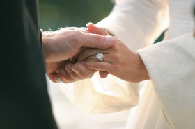 bride wears engagement ring and holds hands with groom