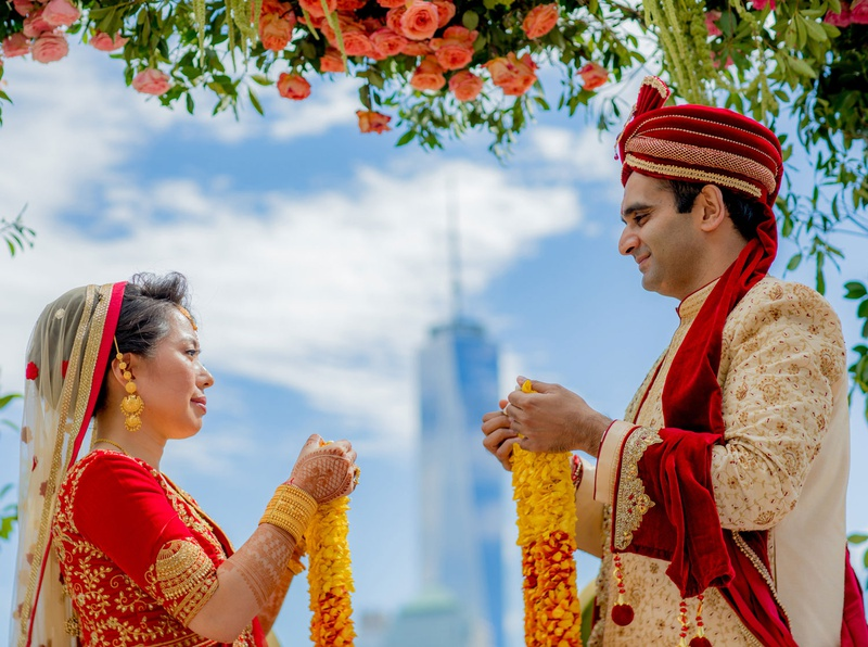 bride and groom indian wedding ceremony outdoor new york skyline view flowers red ensembles