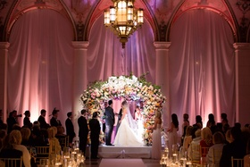 Bride and groom at The Breakers wedding ceremony flower arch chuppah Jewish wedding pink lighting