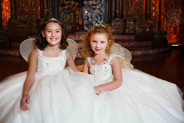 Flower girls in sleeveless white dresses by Matthew Christopher with wings
