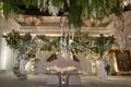 wedding reception with modern sweetheart table banquette seating dream catcher and white flowers