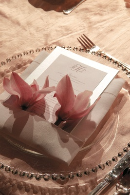 place settings with white linens and two pink flowers
