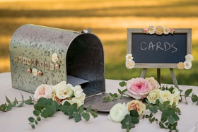 aluminum mailbox with small chalkboard for cards at wedding, roses and eucalyptus