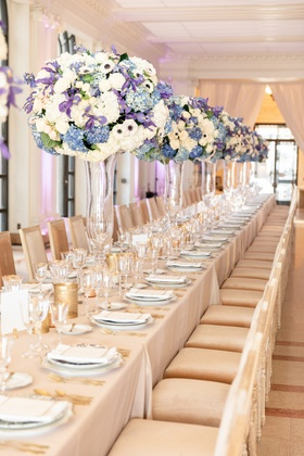intimate wedding reception with tall crystal vases, floral arrangements with blue & white flowers