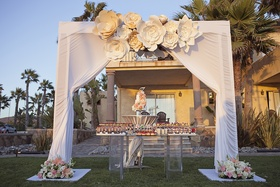 White canopy with flower decorations over wedding cake and dessert table with 200 bite size sweets