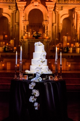 Four layer wedding cake on black table candlesticks orchids cascading down front