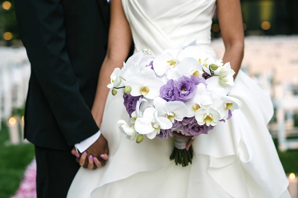 White orchid, purple lisianthus, and purple rose bridal bouquet