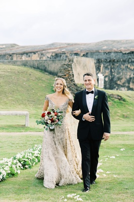 mariana paola vicente walking down aisle with father in tuxedo burgundy bouquet puerto rico fortress