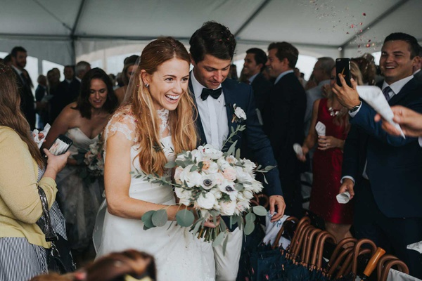happy bride and groom confetti toss guests umbrellas white anemone flower bouquet