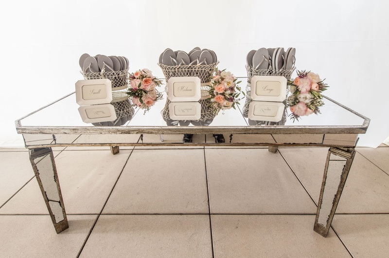 Mirror table with flip flops for guests before dancing at the reception