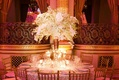Wedding reception centerpiece of white orchids surrounded by vases with floating candles