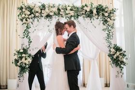 bride in j. mendel wedding dress, groom in suitsupply suit, couple hugging in front of arch