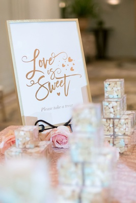 wedding favors on table with gold love is sweet sign ice cream cone gummy candy from sugarfina box