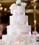Four tier wedding cake sugar flowers pearl dots ribbon detailing fresh flowers