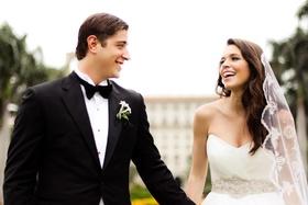 groom wearing black tuxedo and bride wearing mantilla veil