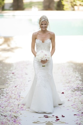 bride in white trumpet gown scalloped neckline holds white pink bouquet walking petal aisle