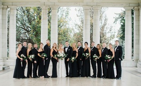 bride in berta wedding dress groom with bridesmaids in black evening gowns groomsmen in tuxedos