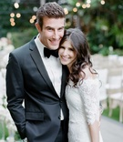 Groom in black and white tuxedo with bow tie smiling with bride in Marchesa wedding dress