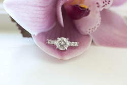 Four-prong round diamond engagement ring on purple orchid