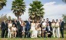 Bride in white v neck sheath dress groom in navy blue suit bridesmaids in jumpsuits and groomsmen