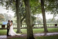 bride in stephen yearick and groom in gold and black jacket kiss outside after it rained