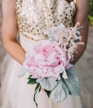 Flower girl in gold and white dress carries pink peony lamb's ear dusty miller