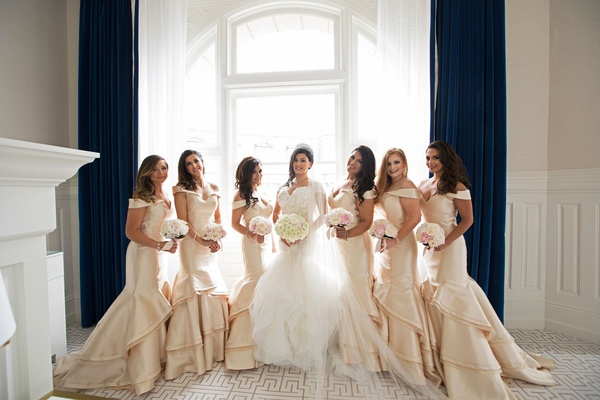 Bride in matthew christopher wedding dress and bridesmaids in off shoulder mermaid gowns gold