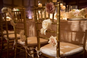 gold chiavari wedding chairs decorated with ivory and blush rose flowers