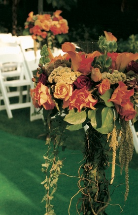 orange flowers and green leaves decorate ceremony aisle