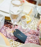 Wedding shower black place cards with names in gold ink tied with gold ribbon to Champagne flute