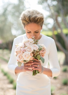 Bride in three-quarter-sleeve wedding dress smells rose wedding bouquet