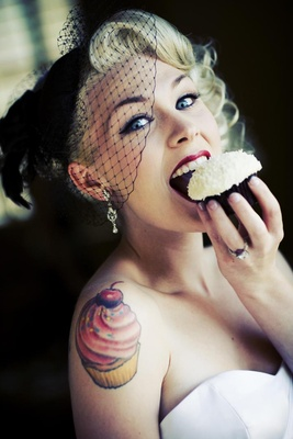 Bride in a black wedge veil eats a Sprinkles cupcake