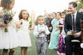 wedding party flower girls in white dresses bouquets purple ring bearer in grey pants suspenders
