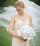 Bride in strapless mark zunino blush mermaid gown holding bouquet white orchids veil blowing in wind